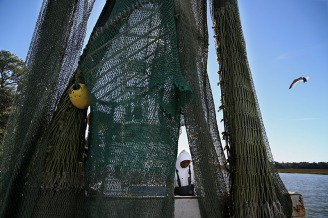 Hanging nets dry after the trip as Bradley works.