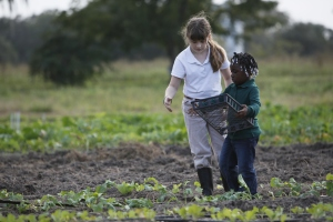 Carolyn Durance, left, and Zariah Green work together to remove weeds during the after-school program.