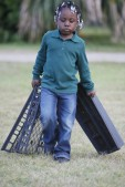 Zariah Green carries boxes across the Marshview Community Organic Farm in order to harvest the greens planted.