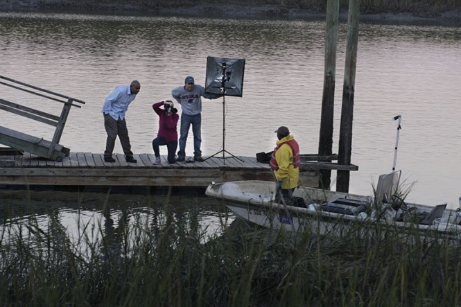Atiba Smith, left, Lee Walker and Jeremy Aaron work from the dock as Earnest Atkins stands for a portrait on his johnboat. Walker and Aaron were visual communications majors at University of South Carolina.